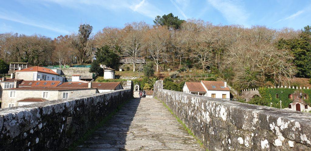 Peregrinos cruzando el puente viejo de Ponte Maceira